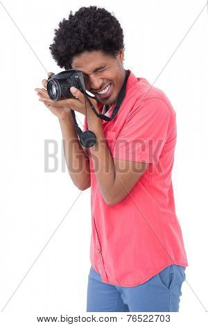 Happy man taking photograph with digital camera on white background