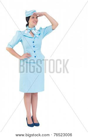 Pretty air hostess with hand on hip on white background