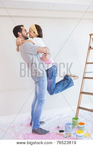 Cute couple hugging while redecorating in their new home