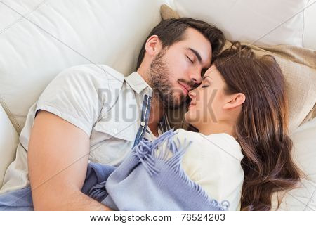 Cute couple napping on couch at home in the living room