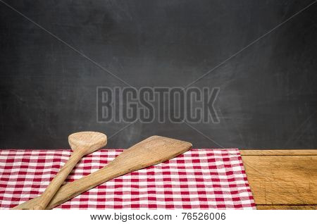 Wooden spoons on a checkered tablecloth in front of a blackboard
