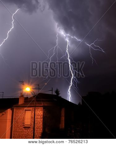 lightning falling behind a house