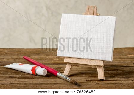 Easel with a blank canvas paint and brush