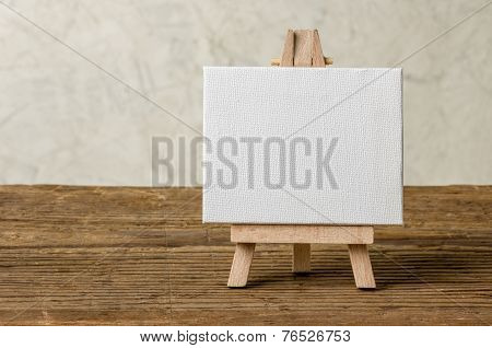 Easel with a blank canvas on a wooden background