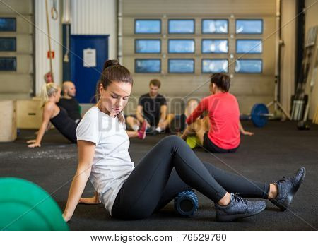 Full length of young woman doing relaxation exercise in crossfit gym