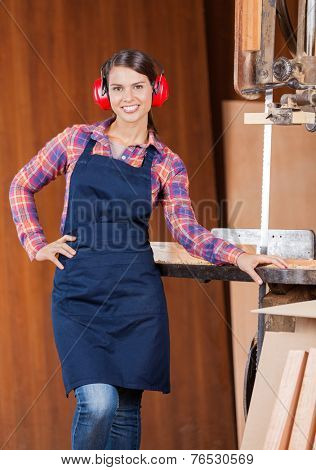 Portrait of confident female carpenter with hand on waist standing by bandsaw in workshop
