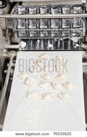 Ravioli pasta on automated machine in commercial kitchen