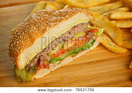Cutted burger with melted cheese and thick succulent ground beef patty, lettuce, tomato, onion, sesa