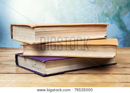 Three Old Books On Wooden Table