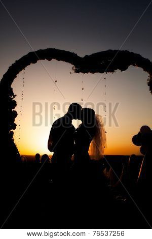 newlyweds kissing at sunset in the arch. silhouette