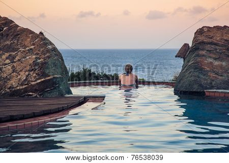 real woman in  pool overlooking the sea  at sunset  in a moment of silence(rear view)