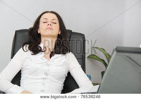 Tired business woman fell asleep next to a laptop