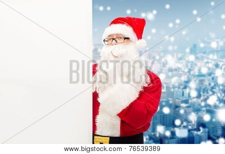 christmas, holidays, advertisement and people concept - man in costume of santa claus with white blank billboard making hust gesture over snowy city background