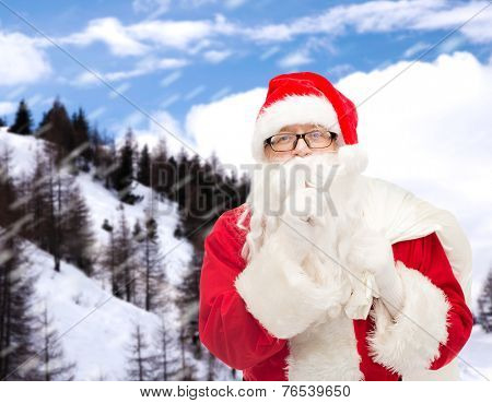 christmas, holidays and people concept - man in costume of santa claus with bag making hush gesture over snowy mountains