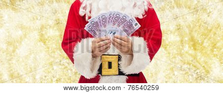 christmas, holidays, winning, currency and people concept - close up of santa claus with euro money over yellow lights background