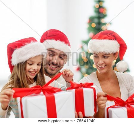family, generation, holidays and people concept - happy family in santa helper hats with gift boxes over living room with christmas tree background
