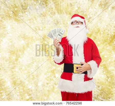 christmas, holidays, winning, currency and people concept - man in costume of santa claus with dollar money over yellow lights background