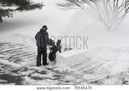 Man Using Snowblower to Clean Driveway