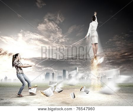Woman holding on rope businesswoman trying to escape