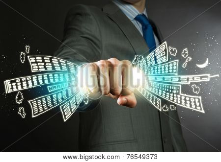 Close up of businessman grasping buildings in fist