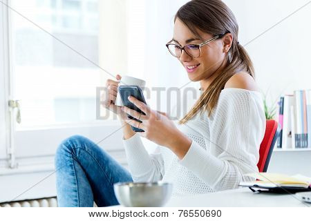 Pretty Young Woman Using Her Mobile Phone In The Office.
