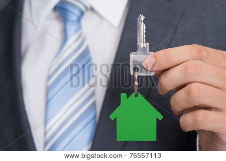 Businessman Holding Key With Green House Keychain