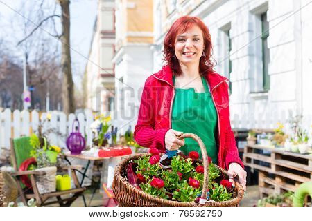 Florist with flower basket in front of shop