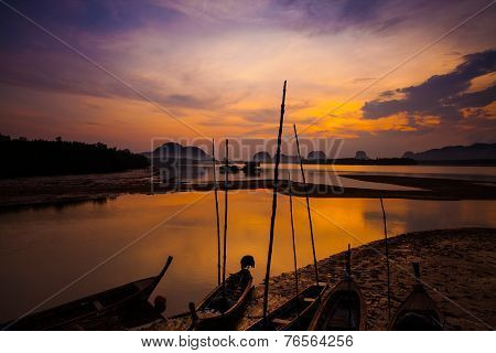 Silhouette of fisherman and traditional thai boats at Sam chong Tai, Phangnga Pprovince.