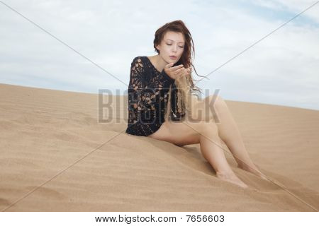 Lady Blowing On Sand Grains