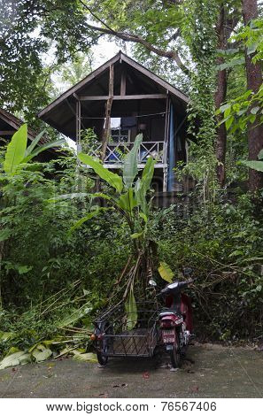 Phuket,TH-Sept,15 2014:Motorcycle with sidecar and poor house of Thais in Sept,15 2014 in Phuket,TH