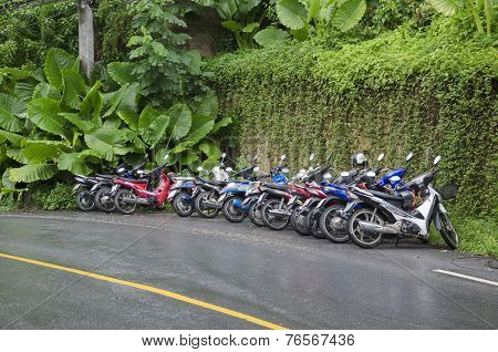 Phuket,TH-Sept,15 2014:Motorbikes stand in a row on wet road in Sept, 15 2014 in Phuket, Thailand