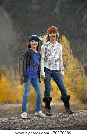 Two Adolescent girls standing on log in outdoor autumn setting