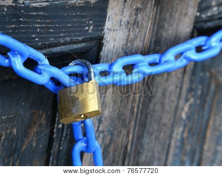 Big Padlock With A Blue Chain And  The Door Closed