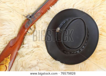 Cowboy hat and hunting guns on a sheep fur.