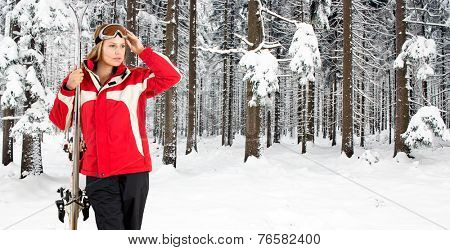 Skiing woman posing in the deep snow woth a forest, covered in fresh, powder snow, in the background