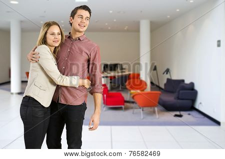 young couple hugging together in the modern, trendy interior of a lounge.
