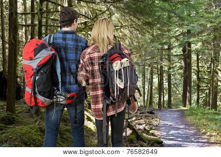 young couple with backpacks looking at the trail in front of them, leading through a dense rain forest