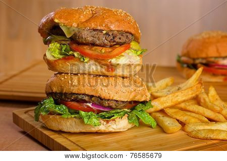 Tasty burgers with melted cheese and thick succulent ground beef patty, lettuce, tomato, onion, sesa