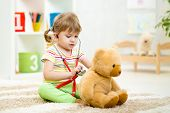 stock photo of heartbeat  - kid girl playing doctor with plush toy at nursery - JPG
