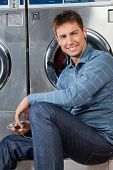 pic of laundromat  - Portrait of young man listening to music while sitting against washing machine at laundromat - JPG