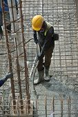 picture of vibrator  - A construction worker using a concrete vibrator at a construction site in Selangor - JPG