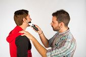 stock photo of electric trimmer  - Barber trimming a beard with an electric razor - JPG