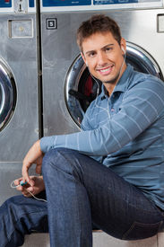 stock photo of laundromat  - Portrait of young man listening to music while sitting against washing machine at laundromat - JPG