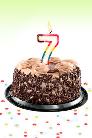 stock photo of number 7  - Chocolate birthday cake surrounded by confetti with lit candle for a seventh birthday or anniversary celebration - JPG