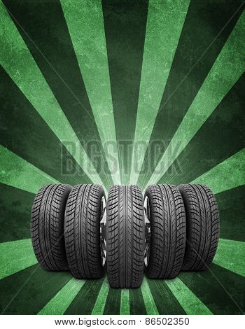 Wedge of new car wheels. Green background is concrete and stripes at bottom