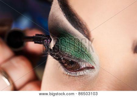 makeup artist paints eyelashes