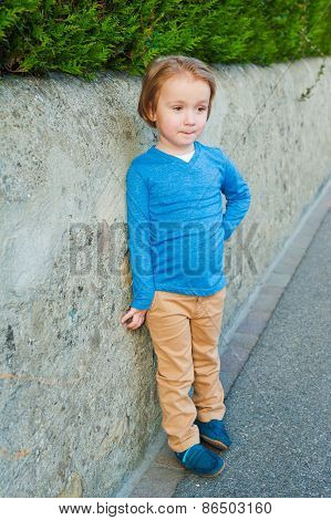 Outdoor portrait of adorable little boy wearing blue t-shirt, beige trousers and dark blue moccasins