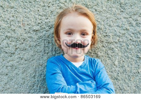 Outdoor close up portrait of a cute little boy with fake italian moustache