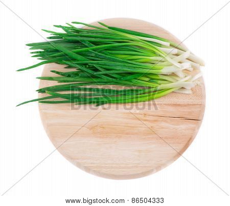Bunch of green onion on wooden platter.