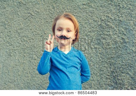 Young cute caucasian boy of 4 years old with a fake Italian moustache